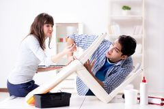 The wife helping husband to repair broken chair at home. Wife helping husband to repair broken chair at home Royalty Free Stock Image