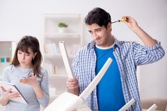 The wife helping husband to repair broken chair at home. Wife helping husband to repair broken chair at home Stock Image