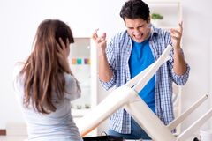 The wife helping husband to repair broken chair at home. Wife helping husband to repair broken chair at home Stock Photo
