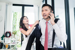 Wife helping man being late for work in jacket Royalty Free Stock Photos