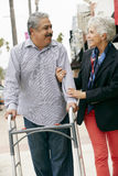 Wife Helping Senior Husband To Use Walking Frame Stock Image
