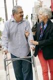 Wife Helping Senior Husband To Use Walking Frame Stock Image