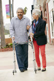 Wife Helping Senior Husband To Use Walking Frame Stock Photo