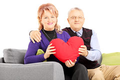 Wife and her husband sitting on a sofa and holding a red heart Royalty Free Stock Photography