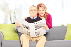 Wife and her husband on a sofa looking at camera at home Royalty Free Stock Images