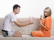 Wife hides from her husband wad of money in a robe sitting on the couch Stock Photos