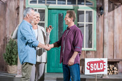 Wife holding keys of new house while her husband shaking hands with saleman Royalty Free Stock Photo