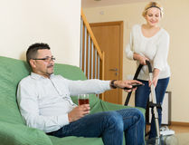 Wife hoovering room, husband relaxing Royalty Free Stock Images