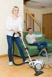 Wife hoovering room, husband relaxing Royalty Free Stock Image