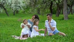 Wife and husband have fun with two daughters sitting on a plaid blanket stock footage