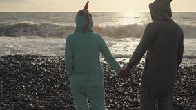 Man and woman in kigurumi are standing on a beach and looking on ocean waves. Wife and husband is holding hands and enjoying view on powerful waves. They are stock video footage