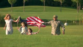 Wife and husband holding one big usa background. Patriotic family running together stock video footage