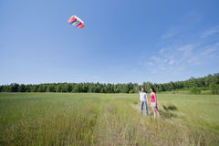 Wife, husband launch kite in field Stock Photos
