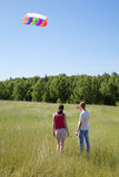 Wife, husband launch kite in field Stock Photo
