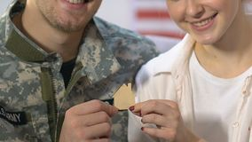 Wife and husband military uniform holding wooden house sign, ownership, mortgage. Stock footage stock footage