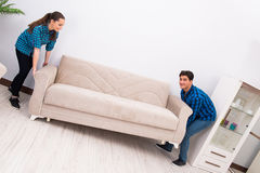 The wife and husband moving sofa couch Stock Image