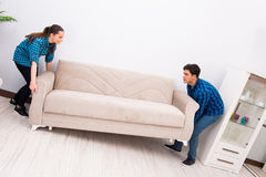 The wife and husband moving sofa couch Royalty Free Stock Photo