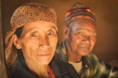 Wife and husband in Nepal. Beni, Nepal - circa May 2012: Native woman with headcloth and piercing in her nose with her husband in background in Beni, Nepal Royalty Free Stock Image