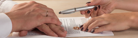 Wife and husband signing divorce documents or premarital agreement Royalty Free Stock Photography