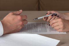 Wife and husband signing divorce documents, woman returning wedding ring. Divorce: hands of wife and husband signing divorce documents, woman returning wedding Stock Photos