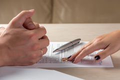Wife and husband signing divorce documents, woman returning wedding ring. Divorce: hands of wife and husband signing divorce documents, woman returning wedding Royalty Free Stock Photo