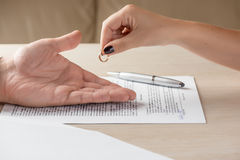 Wife and husband signing divorce documents, woman returning wedding ring. Divorce: hands of wife and husband signing divorce documents, woman returning wedding Stock Photography