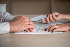 Wife and husband signing divorce documents, woman returning wedding ring. Divorce: hands of wife and husband signing divorce documents, woman returning wedding Royalty Free Stock Photography