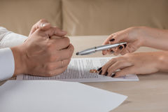 Wife and husband signing divorce documents, woman returning wedding ring. Divorce: hands of wife and husband signing divorce documents, woman returning wedding Stock Image