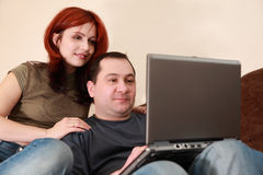 Wife and husband sit and looking at laptop Royalty Free Stock Photography