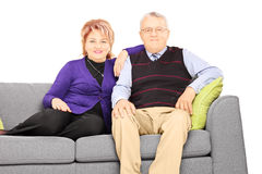 Wife and husband sitting on a modern sofa and looking at camera Royalty Free Stock Photo