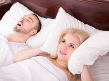 Wife with husband snoring in sleep. Unhappy long-hair wife disturbed with husband snoring in sleep Royalty Free Stock Photography