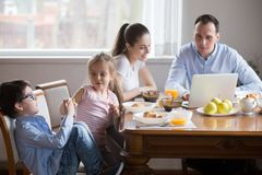 Wife husband using laptop kids have fun with smartphone. Whole family sitting at dining table in kitchen after breakfast at home. Married couple reading news on royalty free stock photos