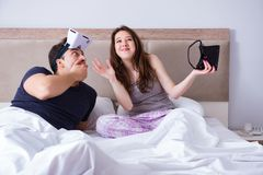 The wife and husband with virtual reality goggles in the bed. Wife and husband with virtual reality goggles in the bed royalty free stock photography