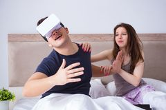 The wife and husband with virtual reality goggles in the bed. Wife and husband with virtual reality goggles in the bed royalty free stock image