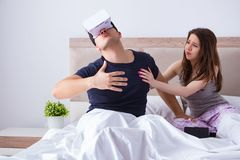 The wife and husband with virtual reality goggles in the bed. Wife and husband with virtual reality goggles in the bed stock image