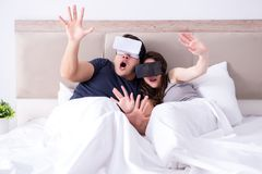 The wife and husband with virtual reality goggles in the bed. Wife and husband with virtual reality goggles in the bed Royalty Free Stock Images