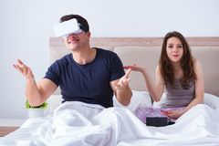 The wife and husband with virtual reality goggles in the bed. Wife and husband with virtual reality goggles in the bed stock images
