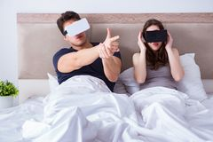 The wife and husband with virtual reality goggles in the bed. Wife and husband with virtual reality goggles in the bed Royalty Free Stock Photos