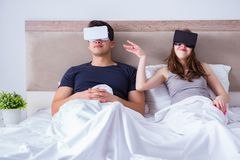The wife and husband with virtual reality goggles in the bed. Wife and husband with virtual reality goggles in the bed stock photos