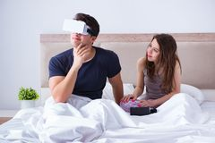 The wife and husband with virtual reality goggles in the bed. Wife and husband with virtual reality goggles in the bed stock photo