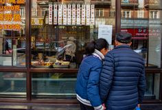 A couple of people window shop at food outlet, Shanghai.