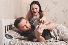 Wife irritate while husband using phone in bed. Royalty Free Stock Photography