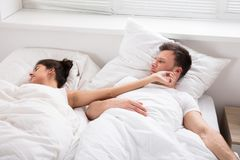 Man Looking At Her Wife Sleeping On Bed Royalty Free Stock Photo