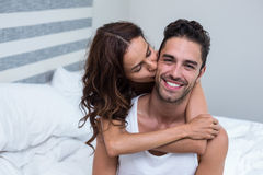 Wife kissing and embracing husband on bed Royalty Free Stock Photo