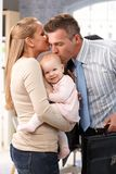 Wife and little girl greeting father arriving home. Businessman father arriving home from work, wife and little baby daughter greeting him with kiss stock image