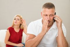 Wife Looking At Husband Talking On Mobile Phone Stock Photography