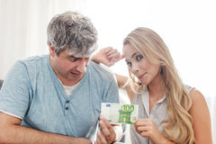 Wife loves money, pulling husbands 100 euros. Indoor Royalty Free Stock Photography