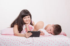 Wife lying in bed with tablet, husband sleeps Stock Photos