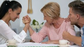 Wife and mother competing hands, fighting for attention of man, arm-wrestling. Stock footage stock video