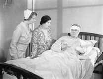 A wife next to her husband in a hospital bed with a nurse attending Stock Photography